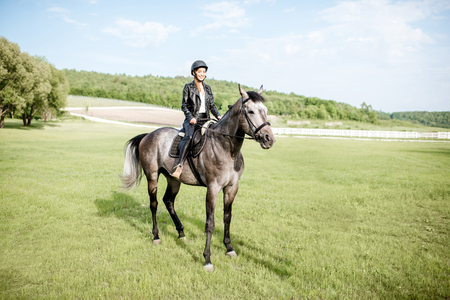 Woman in leather jacket with protective helmet riding a horse on the green meadow Stok Fotoğraf - 101476355