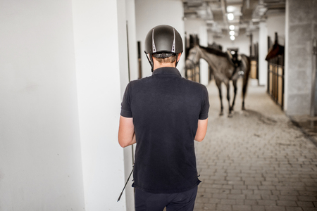 Man prepairing for horse riding standing back in the stable with horse on the backgorund Imagens