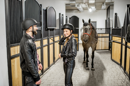 Young couple in leather jackets and protective helmet standing in the horse stable Reklamní fotografie