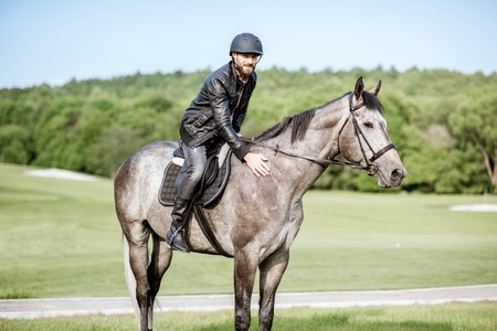Handsome man in leather jacket with protective helmet riding a horse on the green meadow