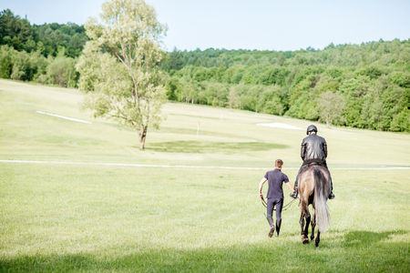 Landscape view on the green meadow with male riders walking back with horse