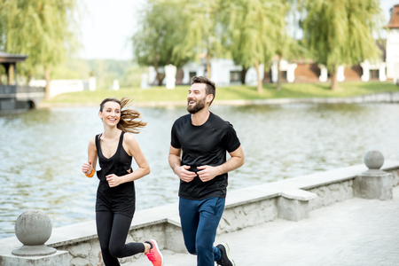 Couple in black sportswear running outdoors near the lake