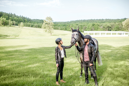Young couple riders standing near the beautiful horse on the green meadow Archivio Fotografico