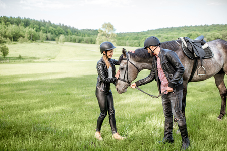 Young couple riders standing near the beautiful horse on the green meadow Reklamní fotografie