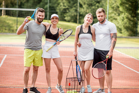 Portrait of a group of young friends in sportswear standing with rackets on the tennis court outdoors