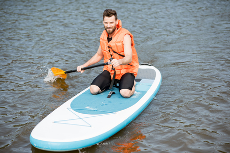 Man in life vest learning to swim with oar on the standup paddleboard on the lake