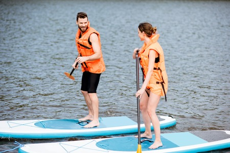 Couple in life vests learning to row on the stand up paddleboard on the lake