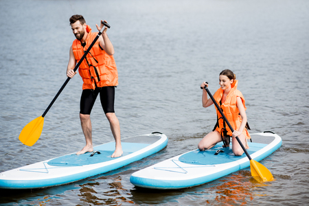 Couple in life vests learning to row on the stand up paddleboard on the lake Stock Photo - 102638724