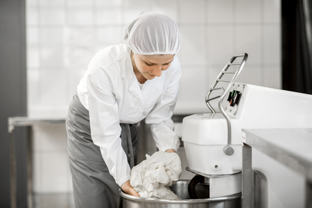 Woman mixing dough with professional kneader machine at the manufacturing Foto de archivo
