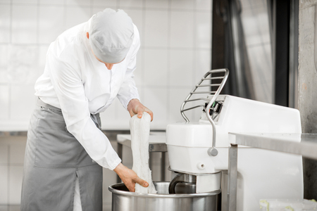 Man mixing dough with professional kneader machine at the manufacturing Banco de Imagens