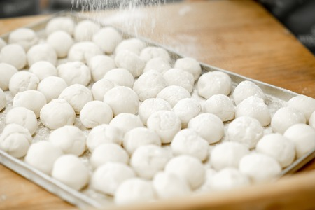 Close-up view on the raw daugh balls ready for baking buns on the tray Standard-Bild - 102692449