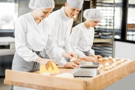 Drie bakkers die plezier hebben met het vormen van deeg om te bakken, staan samen in de moderne productie