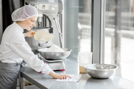 Woman confectioner in uniform weighing ingredients for pastry working at the bakery manufacturing