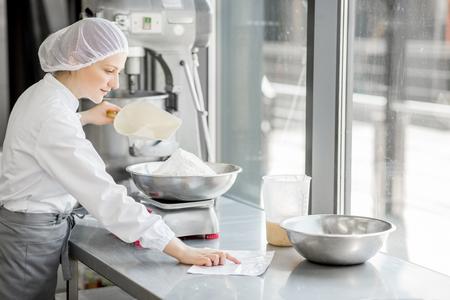 Kobieta cukiernik w mundurze ważenia składników do ciasta, pracująca w produkcji piekarni