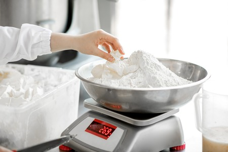 Weighing flour for baking with professional scales at the manufacturing, close-up view