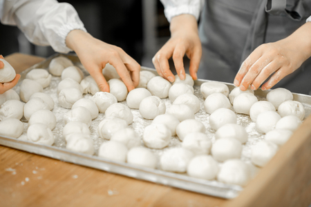 Forming daugh balls for baking buns on the wooden table at the manufacturing