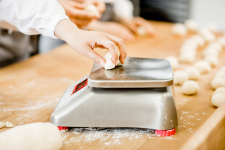 Baker weighing dough portions for baking buns at the manufacturig, close-up view