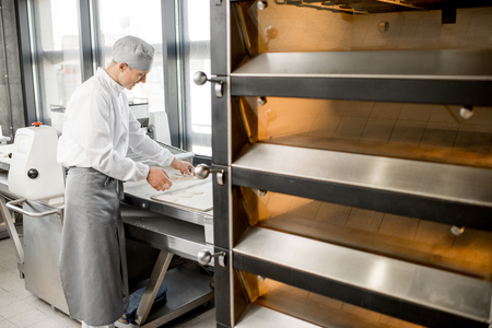 Handsome baker in uniform working with dough rolling machine at the bakery manufacturing
