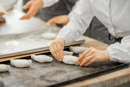 Worker forming raw buns with filling for baking at the manufacturing Standard-Bild - 102812166