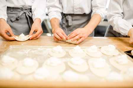 Workers forming raw buns with filling for baking at the manufacturing Standard-Bild - 102812177