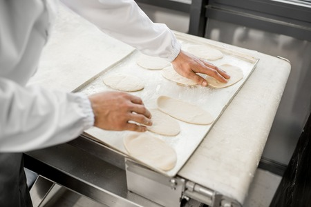 Putting raw dough workpieces for buns making at the bakery manufacturing