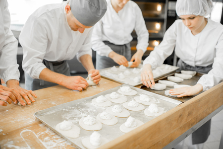 Group of young workers in uniform filling buns for baking on the wooden table standing together at the modern manufacturing