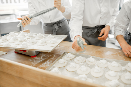 Workers forming raw buns with filling for baking at the manufacturing