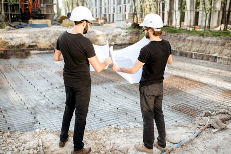 Two builders working with architectural drawings standing on the construction site outdoors