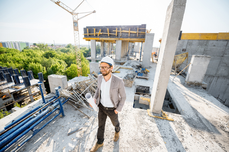 Man supervising the process of house construction walking with drawings on the structure outdoors Banco de Imagens - 102827125