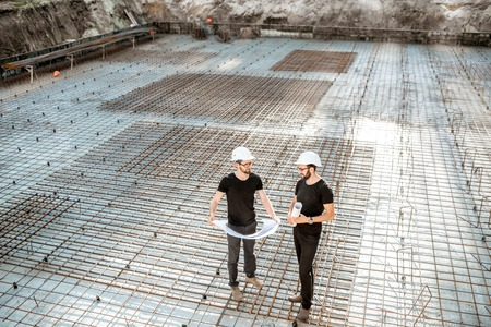 Two builders in t-shirts and protective helmets standing with drawings on the concrete foundation at the construction site