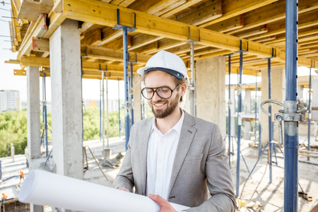 Engineer checking the construction process standing with house drawings on the structure outdoors Stock Photo