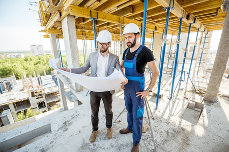 Engineer standing with builder supervising the construction process with house drawings on the structure outdoors
