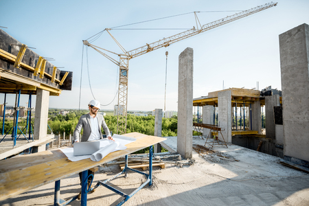 Handsome engineer working with architectural drawings at the table on the construction site outdoors Archivio Fotografico