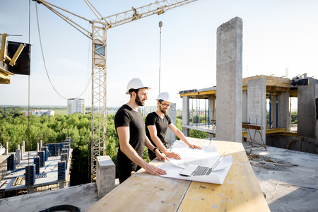 Two workers in black t-shirts and protective harhats working with drawings at the construction site outdoors