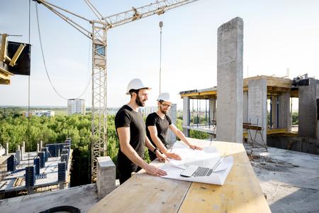 Zwei Arbeiter in schwarzen T-Shirts und Schutzhüten arbeiten mit Zeichnungen auf der Baustelle im Freien