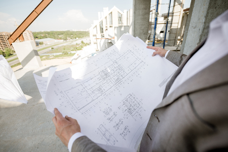 Man holding house plan drawings on the structure outdoors
