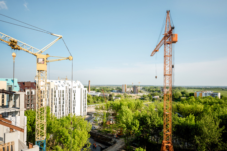 Landscape view on the construction site with building cranes during the sunset Stock Photo