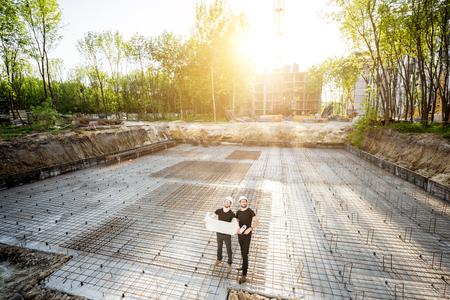 Brede kijkhoek op de betonnen fundering op de bouwplaats met twee bouwers die tijdens de zonsondergang met tekeningen staan
