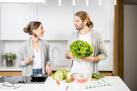 Young cheerful couple dressed alike in gray sweaters cooking some veggie food at the modern kitchen
