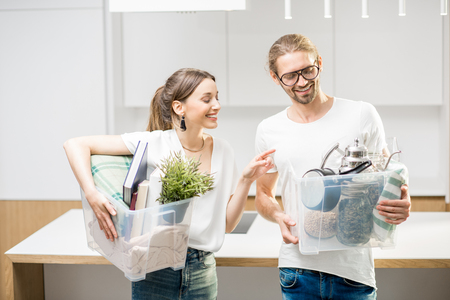 Young and happy couple holding boxes with different home stuff moving to a new modern house Stock Photo