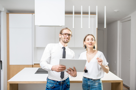 Young couple designing interior standing with digital tablet in the new kitchen interior Standard-Bild - 102826185