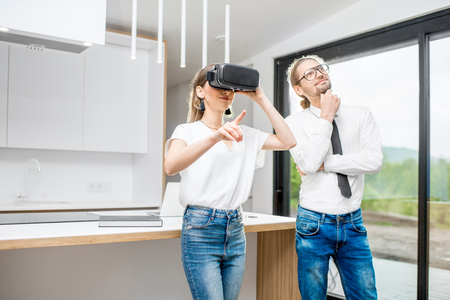 Young couple using VR glasses planning interior standing in the modern kitchen interior