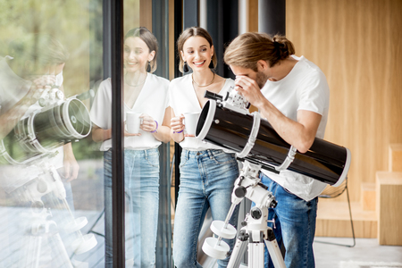 Young couple watching with telescope standing near the window in the modern house