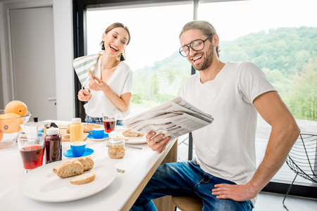 Young couple having breakfast cooking some food and reading newspaper at the kitchen of the modern country house with green area outdoors Фото со стока