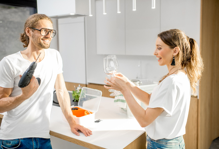 Young couple unpacking different home stuff moving to a new modern apartment