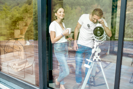 Young couple in white shirts standing with telescope watching stars near the window Stok Fotoğraf