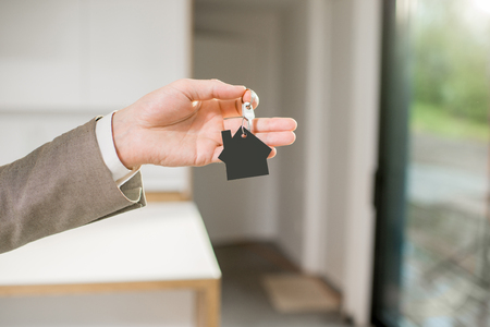 Man holding keys with house keychain in the new home intreior