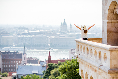 View on the wall of Fisermans bastion with woman standing on the terrace enjoying great view on Budapest city in Hungary Imagens