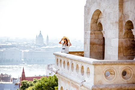 View on the wall of Fisermans bastion with woman standing on the terrace enjoying great view on Budapest city in Hungary Stock Photo