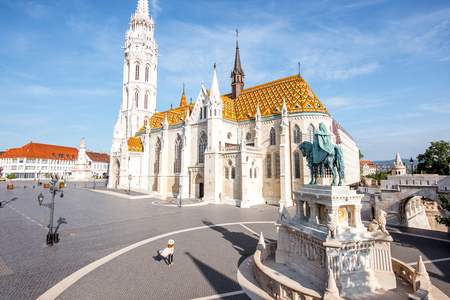 Morning view on the famous Matthias church with bronze statue of Stephen and woman walking in Budapest, Hungary